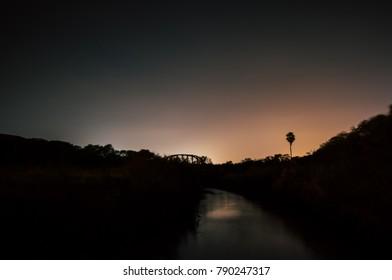 The sun setting behind a bridge