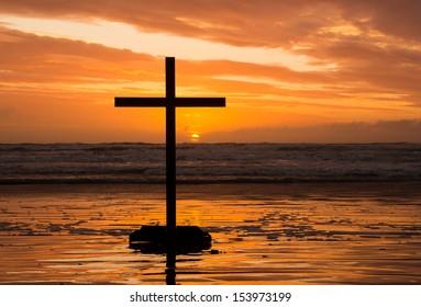 Sun setting behind a cross on a beach.