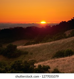 Sun setting behind fog over Pacific Ocean, from mountains of Coastal California