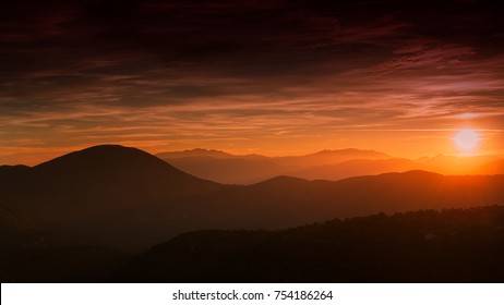 sun setting behind layered, silhouetted mountains