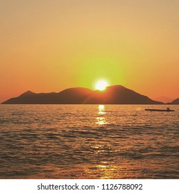 sun setting behind the mountain peak near sea