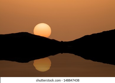 Sun Setting Behind Mountains over a Lake with Reflection