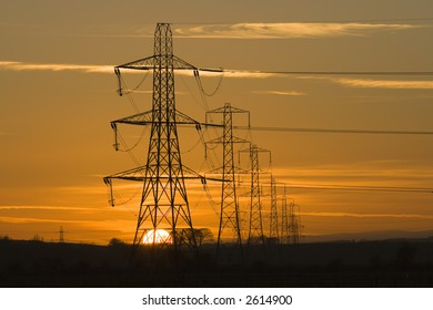 Sun setting behind a row of electricity pylons