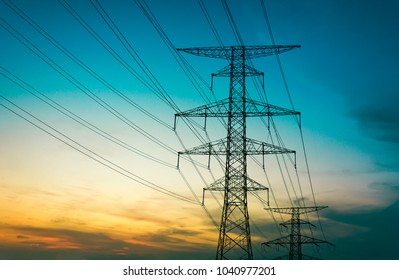 Sun setting behind the silhouette of electricity pylons