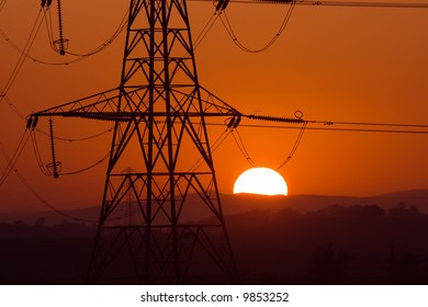 Sun setting behind a silhouetted electricity pylons