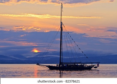 The sun setting behind the Sloop Clearwater  on the Hudson River out for a sunset cruise