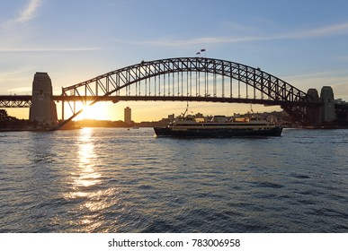 The sun setting behind the Sydney Harbour Bridge with the Manly Ferry in the foreground