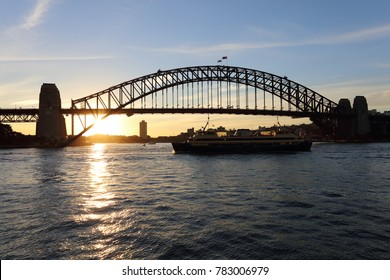 The sun setting behind the Sydney Harbour Bridge with the Manly Ferry in silhouette in the foreground