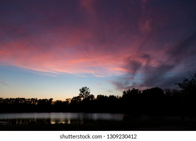 The sun setting behind trees and reflecting color on wispy clouds in a blue sky and on a shadowy pond.