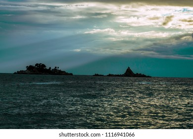 Sun setting between clouds above the wavy sea and islands