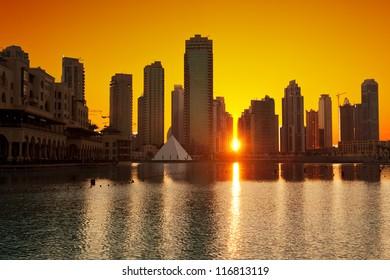 Sun is setting between the modern skyscrapers in Dubai, UAE