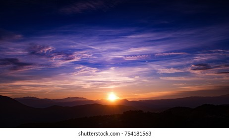 sun setting in a blissful blue sunset sky with scattered clouds