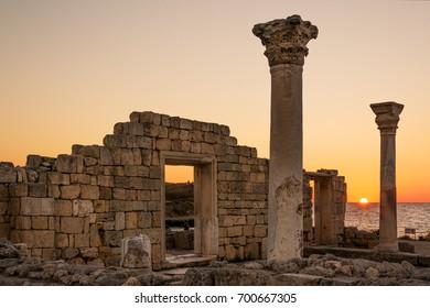 Sun setting by ancient basilica columns of Creek colony Chersonesos in Sevastopol, Crimea