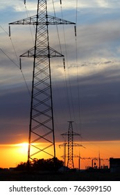 Sun setting by silhouette of communication tower (Pylons at sunset)