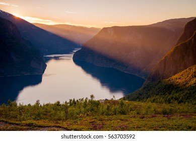 The sun setting and casting its last rays over Aurlandsfjord in Norway