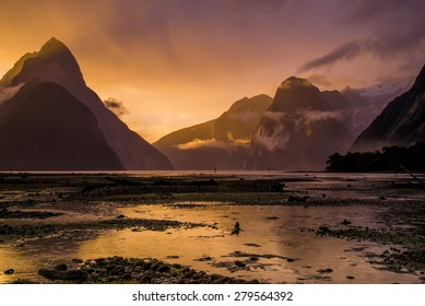 The sun setting dramatically on the fjords of Milford Sound after the rain