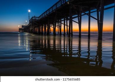 Sun setting at dusk behind the Newport beach pier California