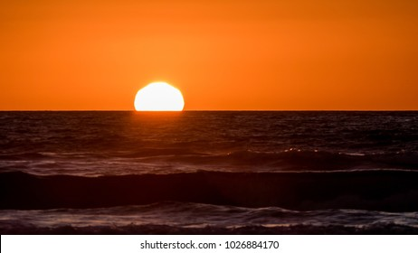 Sun setting low over the ocean