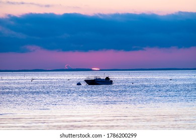 Sun setting on the ocean horizon behind isolated boat in the water.