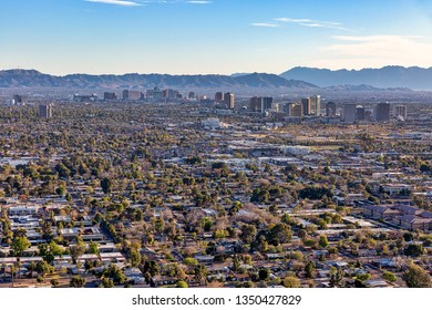 Sun setting on Phoenix, Arizona, aerial view looking northeast to the southwest with midtown and downtown skylines in the distance