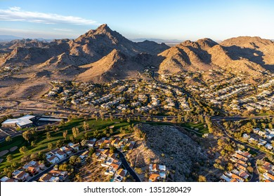 Sun setting on Piestewa Peak and the Phoenix Mountain Preserve, aerial view with upscale golf course and homes in the foreground