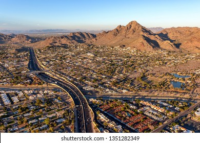Sun setting on Piestewa Peak and the Piestewa Peak Parkway (Arizona State Route 51) in Phoenix, aerial view looking from the southwest to the northeast