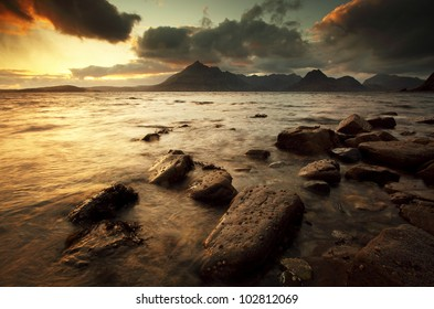 Sun setting on the rocky coastline of Elgol on the isle of Skye, with the Cuillin mountains in the distance and darkened clouds closing in for some stormy weather.