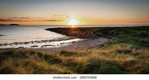 Sun setting on the sand dunes at  Ballyheirnan Beach in Donegal Ireland