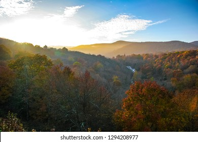 The sun is setting over the beautiful Smoky Mountains in Autumn along the Blue Ridge Parkway in NC. The mountains and treetops are awash in sunlight, and the flowing river is seen below.