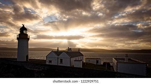 Sun setting over Bressay Lighthouse, Bressay, Shetland, Scotland, UK.