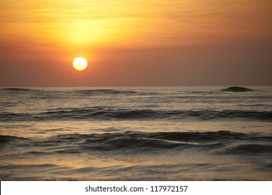 Sun setting over the calm ocean with an orange glow