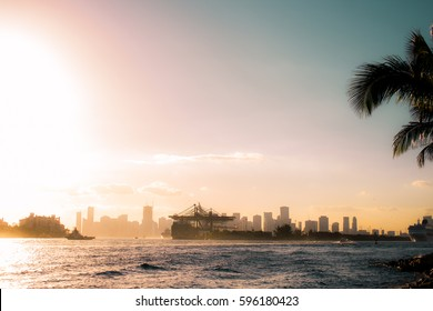 sun setting over city scape over miami at dusk