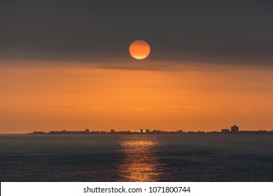 Sun setting over city.  The sun sets ovel the port of El Callao near Lima, Peru.