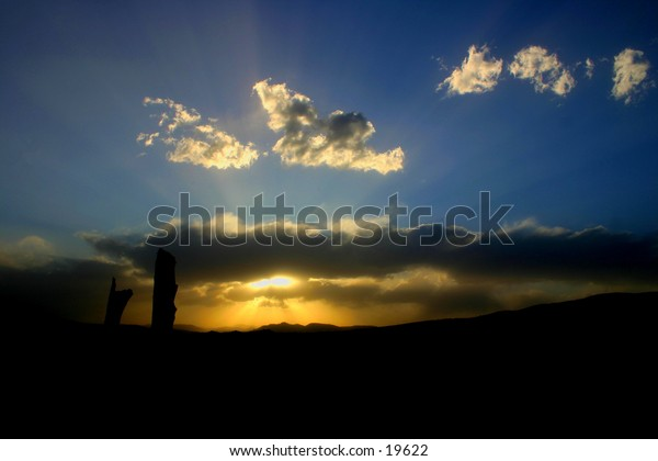 Sun setting over Colorado mountains cast rays over and under cloud bank.