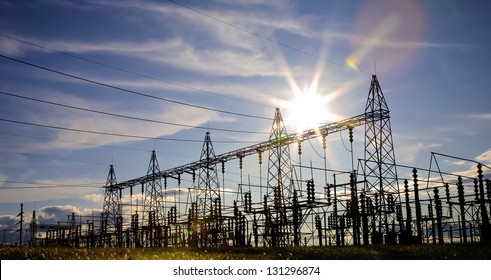 Sun setting over an electrical substation.