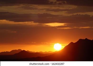 Sun setting over hills