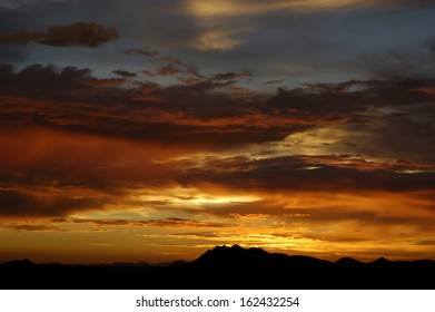 Sun setting over hills with dramatic sky
