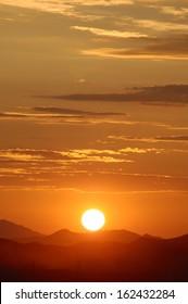 Sun setting over hills (vertical)