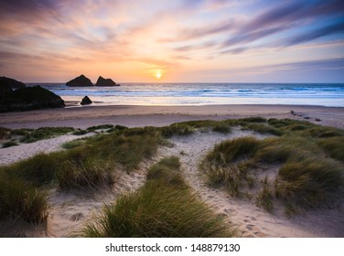 The sun setting over Holywell Bay Beach viewed from the Sand Dunes, Cornwall England UK