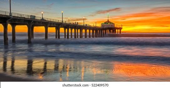 sun setting over manhattan beach pier,as powerful waves roll in,and a very colorful sky is reflected on the beach. manhattan beach,California