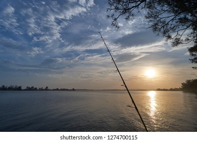 The sun setting over the mighty Clarence River - a fishing rod in the foreground, wispy clouds overhead and a casuarina tree - taken in springtime, while fishing from Goodwood Island, NSW, Australia.