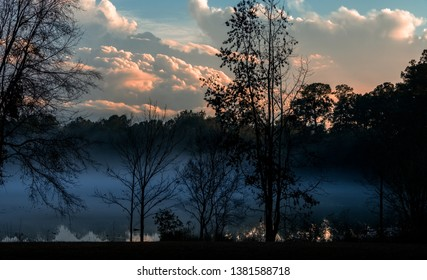 Sun setting over a misty lake in Tallahassee, Florida