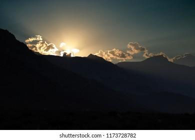 Sun setting over mountain range with sunrays