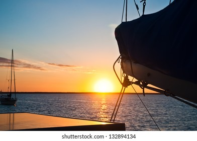 Sun setting over the ocean with the boom and mainsail of a sailboat in the foreground and another boat anchored in the distance copy space available