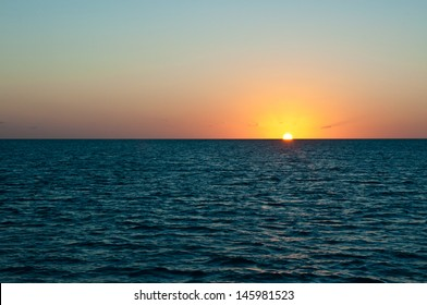 Sun setting over the ocean on a cloudless and clear beautiful night in the bahamas