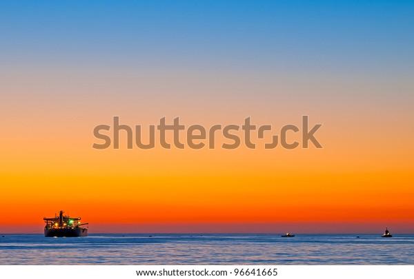 sun setting over the pacific ocean as commercial boats are anchored near el porto, north manhattan beach,california.