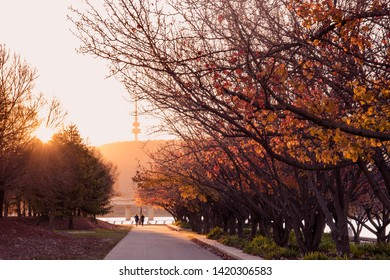 Sun setting over the Queen Elizabeth Terrace along the bank of Lake Burley Griffin by the Commonwealth Place, Canberra, Australian Capital Territory, Australia in late Autumn