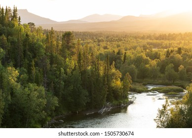 The sun setting over a river in a  green, mountain wilderness. Jamtland, Sweden.