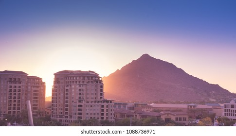 Sun setting over Scottsdale, Arizona waterfront area with Camelback Mountain glowing.