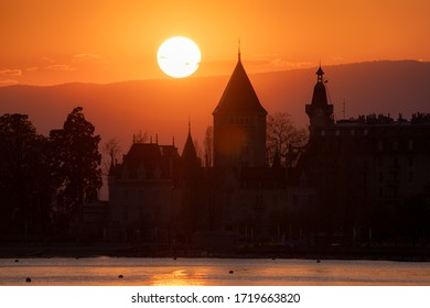 The sun is setting right behind the Chateau d'Ouchy in Lausanne, Switzerland. This castle is right on the waterfront of Lake Geneva.